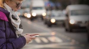 Using cellphone outdoors while crossing the street.